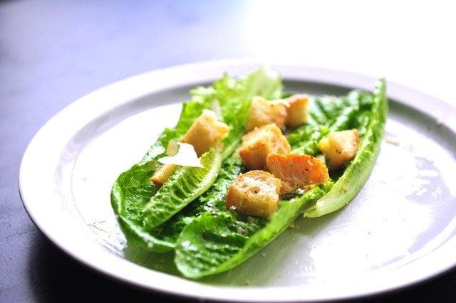 最初的凱撒沙拉,麵包切成塊用蒜泥調味後煎製,與磨碎的帕瑪森芝士一起放到整片生菜上,以便直接用手取食。